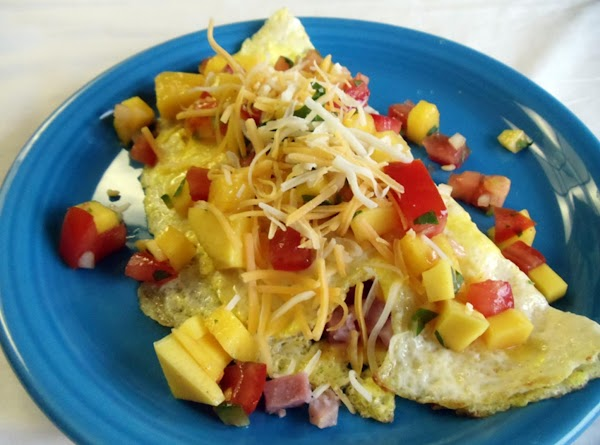 Cover omelet with mango salsa.  Sprinkle with extra shredded cheese, salt and pepper...