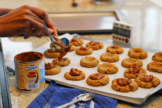Photo: We left the walnuts off of our cookies because of a tree nut allergy. After baking the cookies, Jocelyn addeddulce de leche to the thumbprints in our cookies.