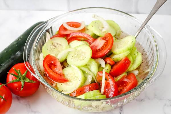 Marinated Cucumbers, Onion, And Tomatoes In A Serving Bowl.