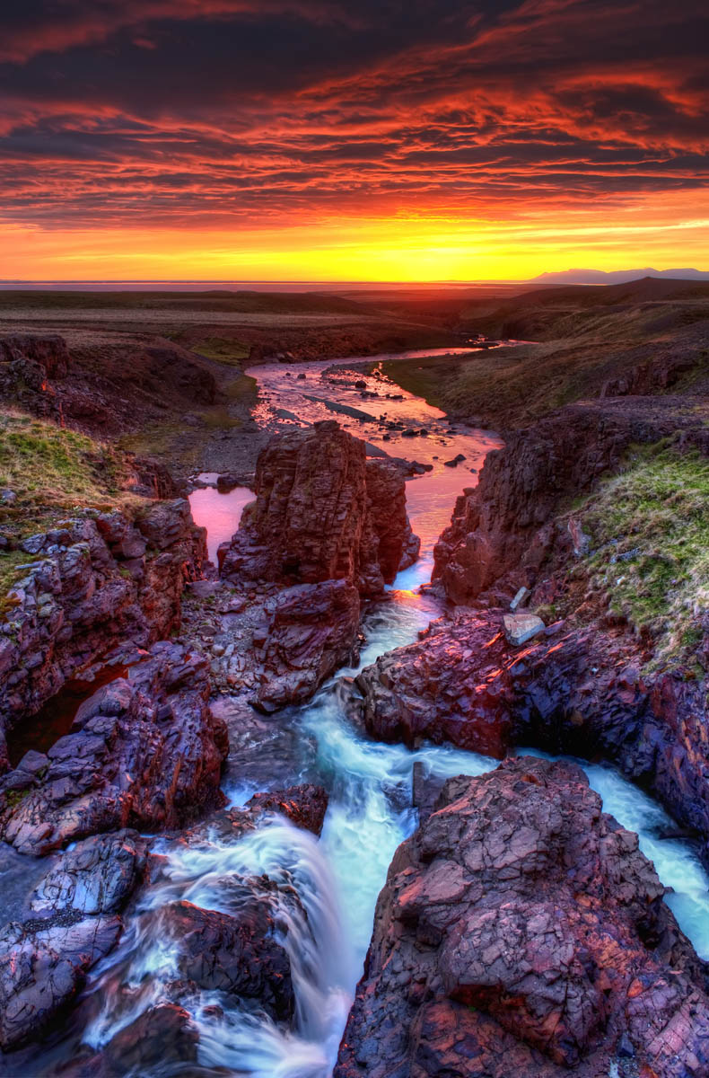 Photo: The Solstice   This came from one of my favorite nights in Iceland! This was shot around 2 AM, right when I started feeling loopy. I was on the edge of some precipitous volcanic rock, and there was a waterfall behind me. It fed this little area of rapids that emptied out into one of the fjords. There had been a light rain for a few hours, but the setting sun cut underneath the clouds to unleash some godly colors.     from the blog www.stuckincustoms.com