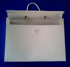 Photo: Maleta pequena com fecho e alça para usos diversos (visão de cima).