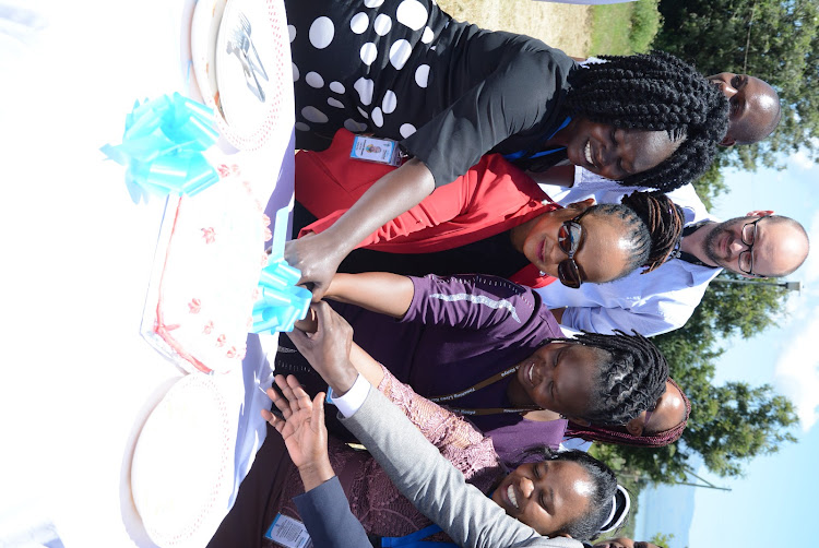 Kenya Accreditation Services (KENAS) Assistant Director in charge of safety and health Dorris Mweni (in glasses) joins staff from AIC Kijabe Naivasha in cutting a cake after the facility laboratory accredited.