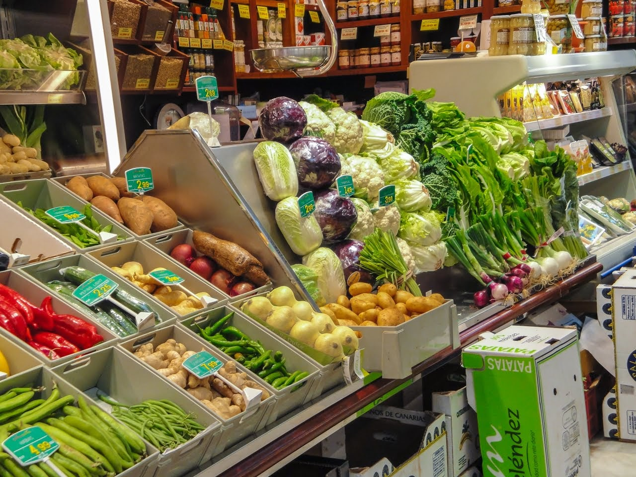 A vegetable vendor's stand featuring local cabbage, potatoes, onions, ginger, and more