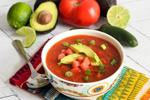 A Bowl Of Spicy Gazpacho Topped With Avocado, Tomatoes, And Green Onions.