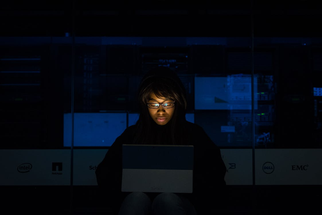 A person works on a laptop in a dark room