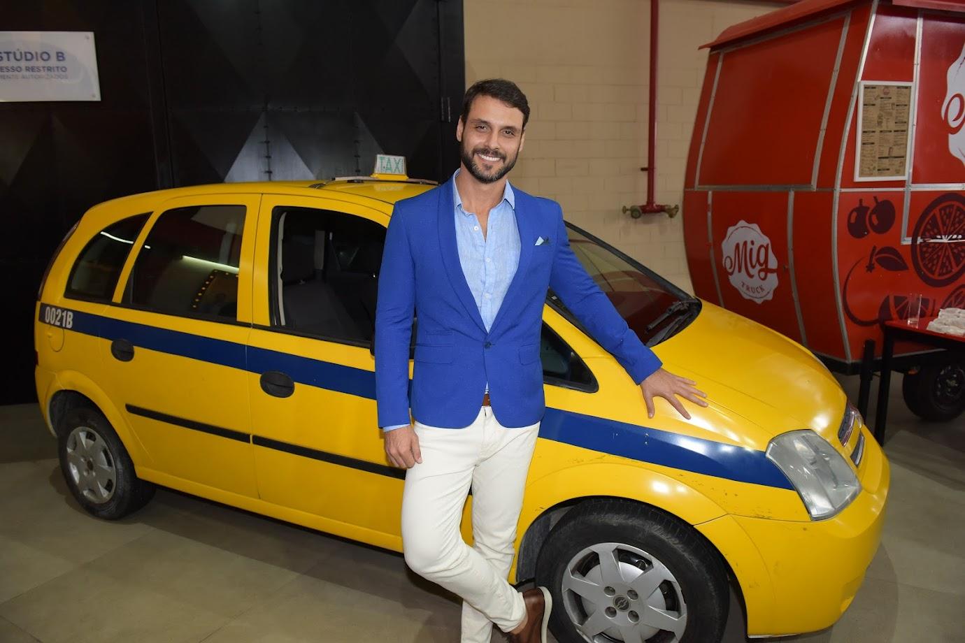 Felipe Cunha posa ao lado do táxi do seu personagem em Topíssima, Antonio