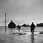 mensen in voetdiep water dat van links naar rechts stroomt