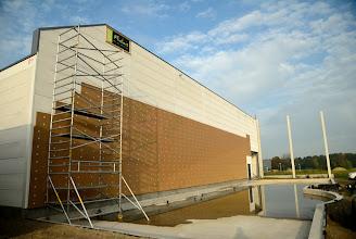 Photo: © ervanofoto 24-10-2012 Intussen hebben de mannen van Flidais al een groot deel van de voorgevel van het magazijn geïsoleerd.