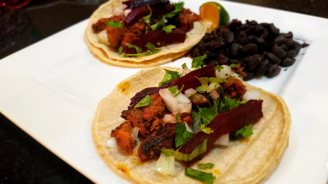 A close up of tacos al pastor with black beans and lime. Toppings include onions, cilantro, and roasted beets.