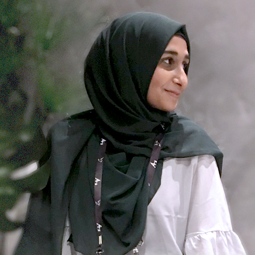 Muslim woman sitting down and wearing a headscarf, or hijab