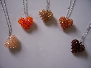 "Photo: Swarovski Crystal Heart. Size: 1"" x 1"" face and 1/2"" thick with 18"" chain. Color left to right: Peach, Fire Opal, Topaz light, Topaz AB and Topaz smoked. $35.00 each."