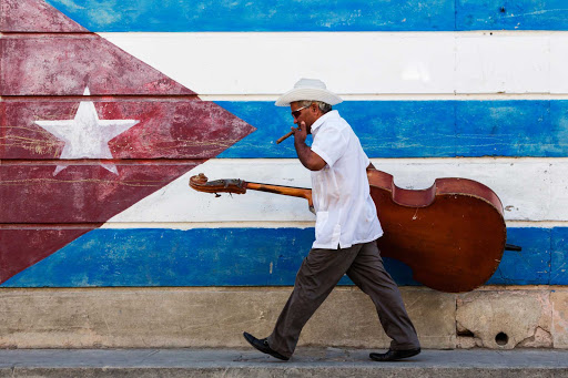 Cuban-Man-Carrying-Base-in-Front-of-Painted-Cuban-Flag.jpg - Visit Cuba on a cruise to hear local musicians in Havana and Cienfuegos.