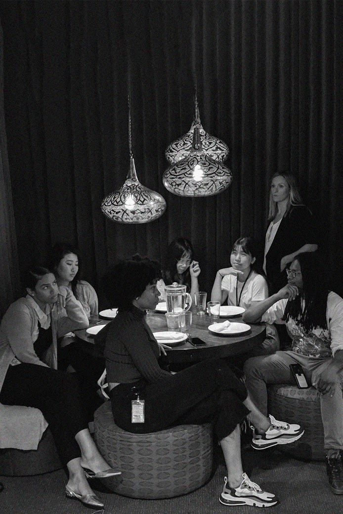 Group of people sitting around a circle table waiting for dinner