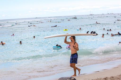 waikiki-beach-surfboard.jpg - A surfer strolls along Waikiki Beach.