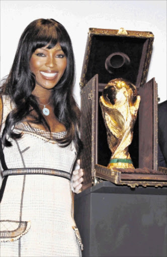 Model Naomi Campbell poses with the World Cup trophy which is presented in its Louis Vuitton travelling case in Paris June 1, 2010. Louis Vuitton and FIFA collaborated on the new travel case for the FIFA World Cup trophy and it will be used for the first time at the World Cup in South Africa.  REUTERS/Jacky Naegelen   (FRANCE - Tags: SPORT SOCCER WORLD CUP BUSINESS FASHION)