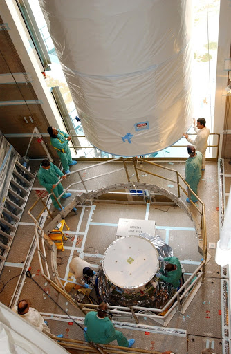 Inside the mobile service tower workers help guide the Aura spacecraft toward the second stage of the Boeing Delta II rocket.