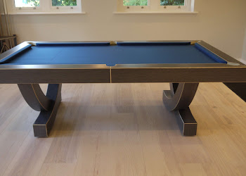 the arc pool table with black legs on light wooden flooring