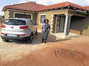 Jeremia Ngwenya's wife, Sibongile, stands next to the Kia Sportage whose computer box was allegedly ruined at the dealership he had taken it to for repairs.