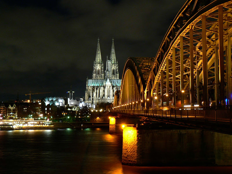 The Railway Bridge and the Cologne Cathedral at night during the holidays. At left is the floating Christmas market on the Rhine.