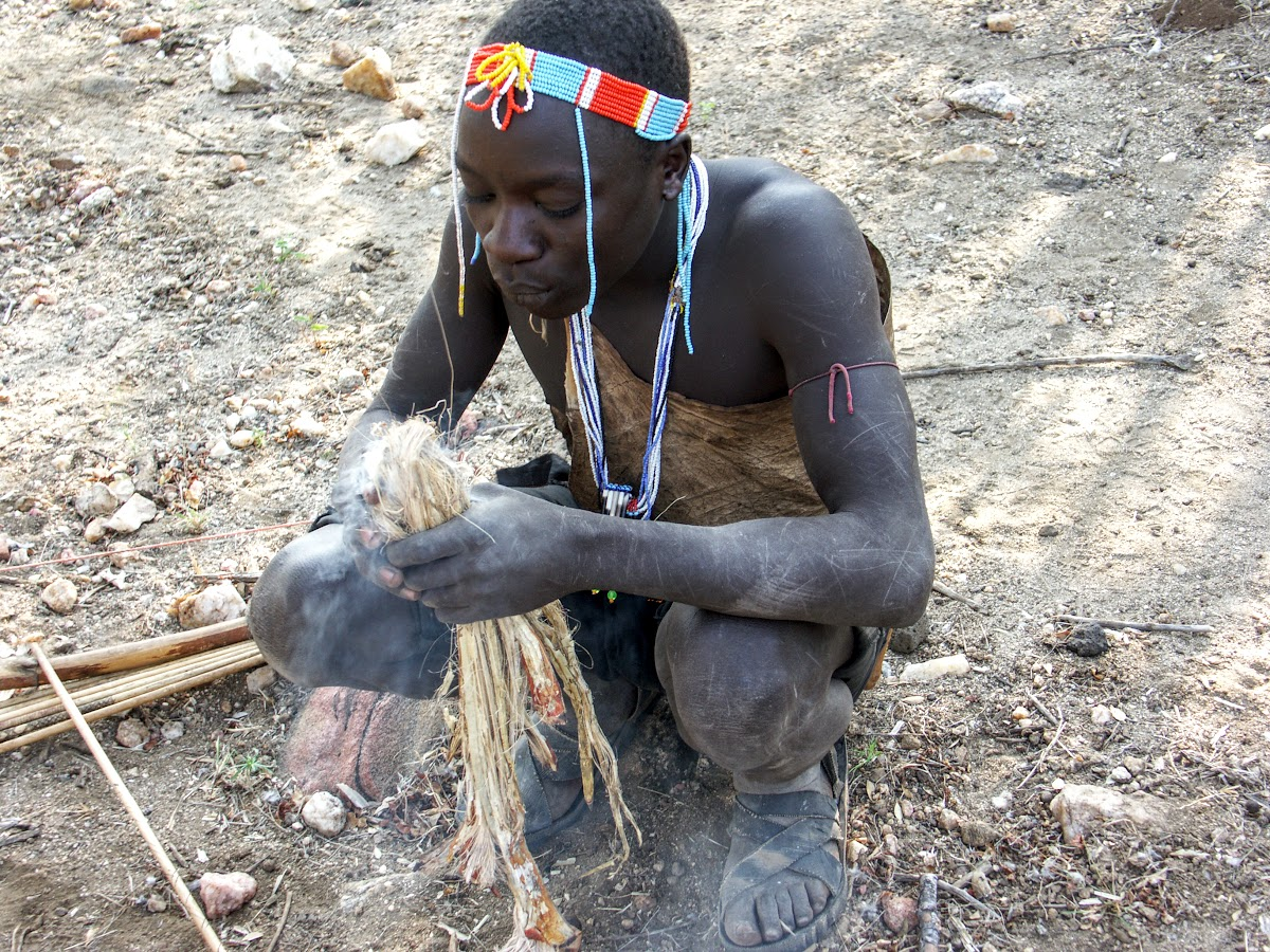 Hunter preparing a fire to cook the birds