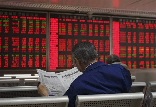 An investor reads the finance section of a newspaper at a brokerage in Beijing.   Picture: REUTERS