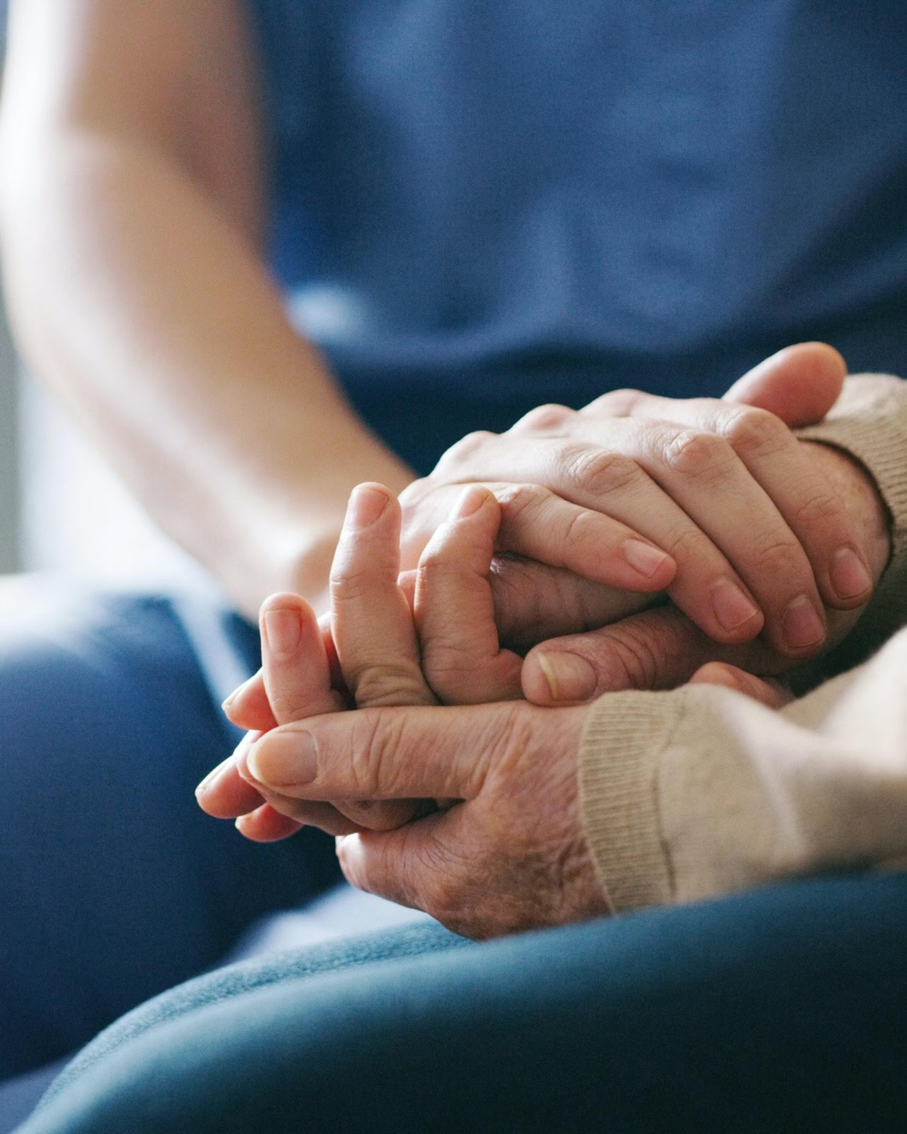 A senior woman holding hands with a nurse