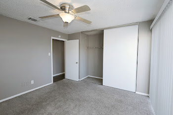 Bedroom with brown carpet, light brown walls, and ceiling fan