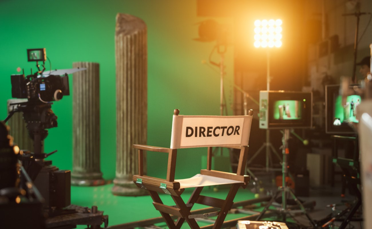 ALT: A director's chair on a green screen set.