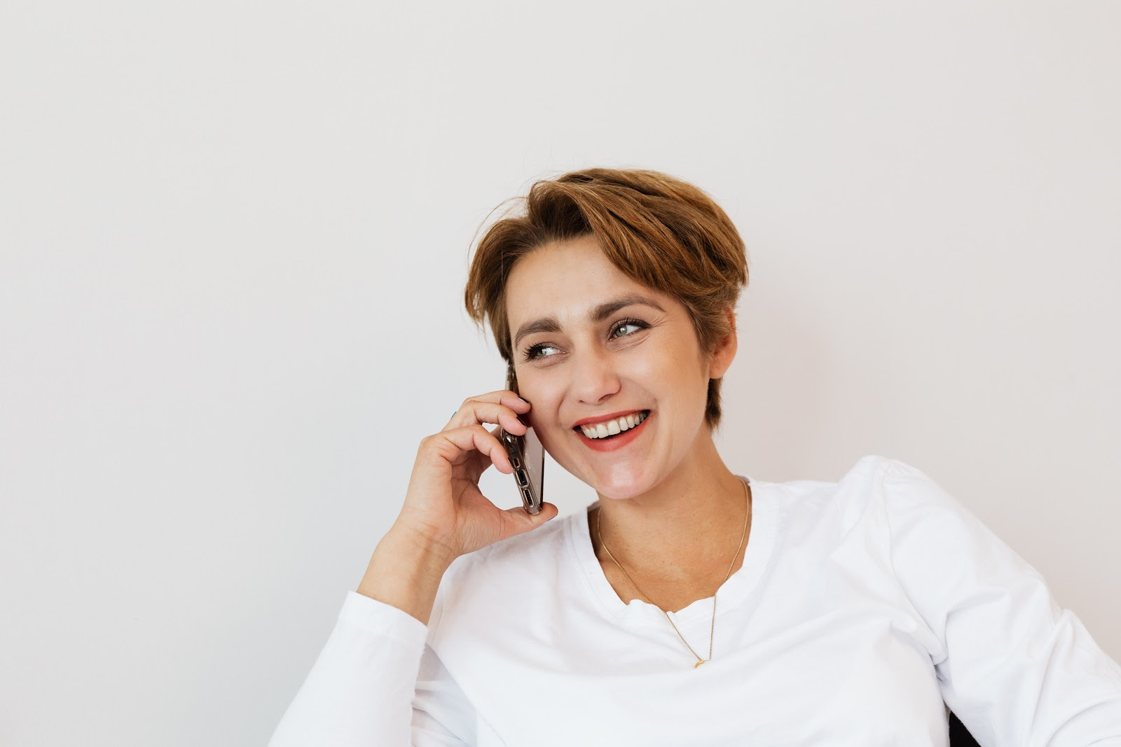 A woman happily talking on phone to her friend as a measure to cope with anxiety