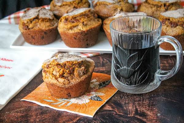 Cinnamon Chip Pumpkin Muffin On A Napkin With A Cup Of Coffee.