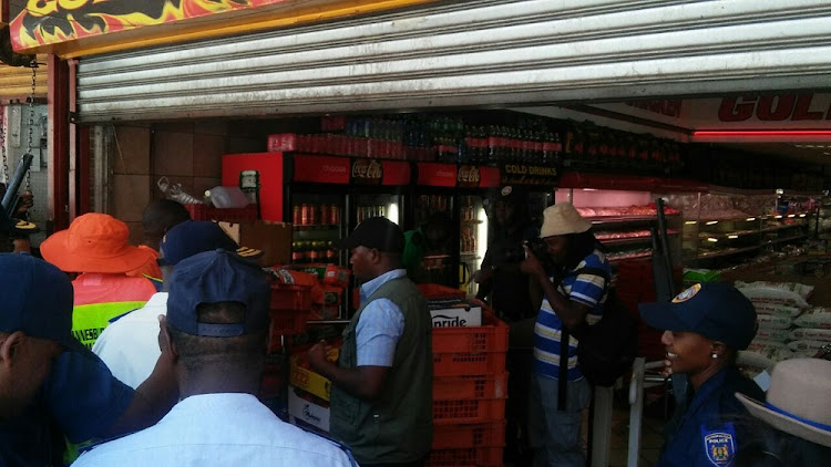 Joburg mayor Herman Mashaba ,in orange hat, shuts down a butchery in Yeoville for illegal electricity connection and failure to comply with health and safety standards.