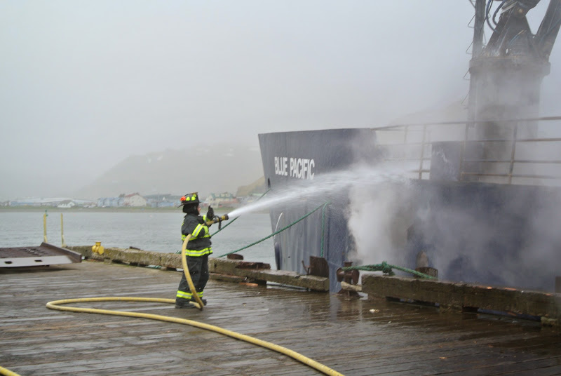 Photo: A firefighter sprays down the F/V Blue Pacific at the Coastal Transportation dock.
