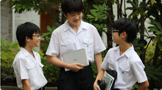 Three young male students wearing identical white collared shirts stand talking to each other and smiling.