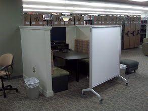"Photo: booth-type seating around large screen facilitates group work. portable white boards can be used to write on but staff say they are more commonly used to enclose group spaces, creating a private ""room""."