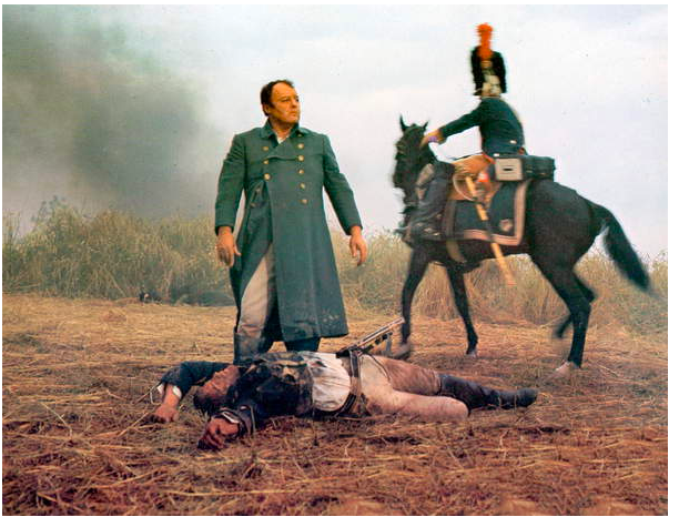 Image of a film still presenting a scene at the Battle of Waterloo, a man lies injured on the ground with Napoleon standing above him with an assertive manner, actor is Rod Steiger © Dino de Laurentiis Cinematografica/Mosfilm / Collection CSFF / Bridgeman Images
