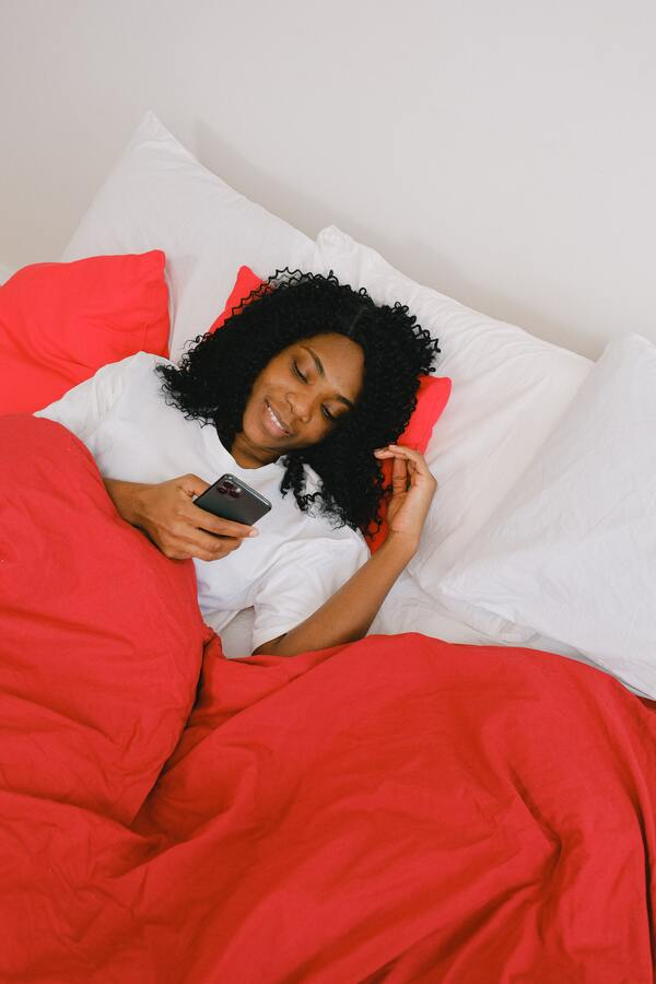 mulher negra deitada na cama usando o celular