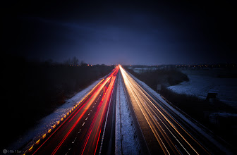 Photo: As You Head For Home  Standing on a flyover watching the breath freeze as it leaves my mouth and the cold chills my bones you all head for home. Car after car pass by, each with a story, a tale of the day, a reason for being on this road, some just another day, some with much more to tell. But each car just passes by and leaves behind nothing but its lights caught in a lens as it disappears into the distance along with its story, with its tale of the day. I wonder who you are, where you are going and where you have been been, but like my breath that freezes in the air you are fleeting.