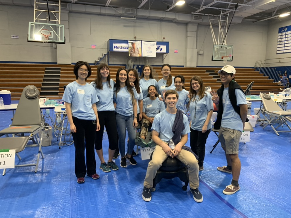 A group of college students wearing matching t-shirts smile at the camera. One girl sits in a dental chair, one boy sits in the dentist's chair. They are in a school gym with blue tarpaulin on the floors.