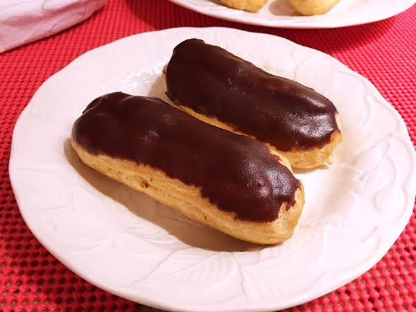Two Chocolate Eclairs On A White Plate.