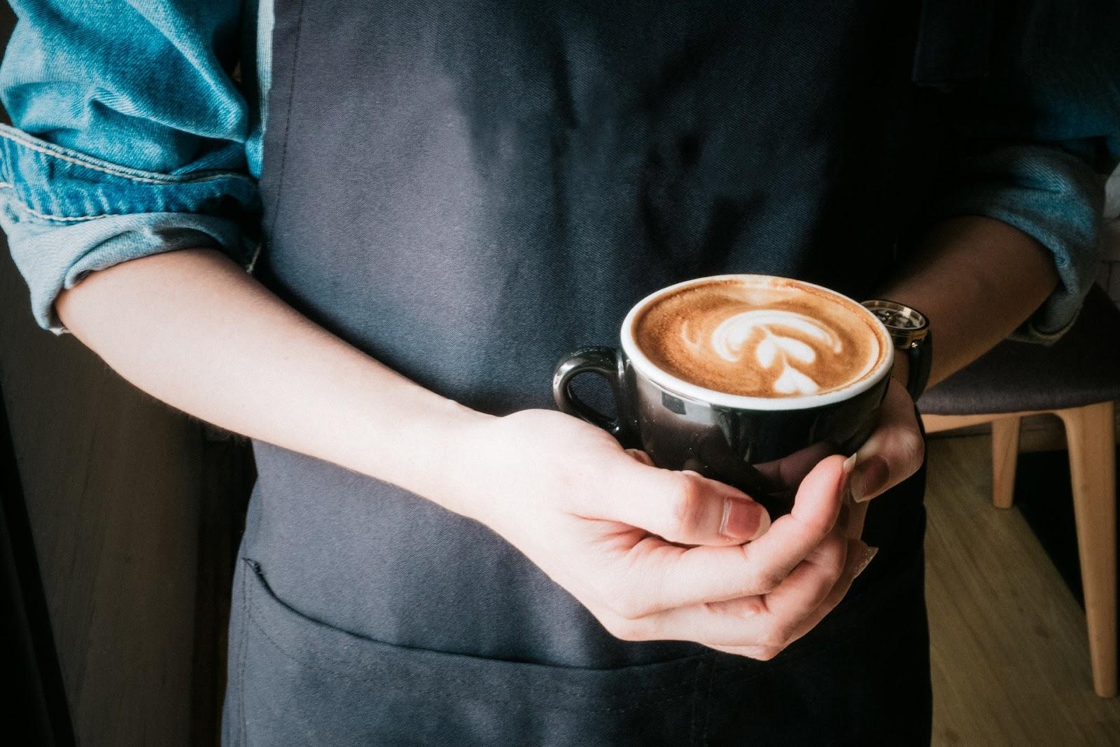 pessoa segurando copo café decorado