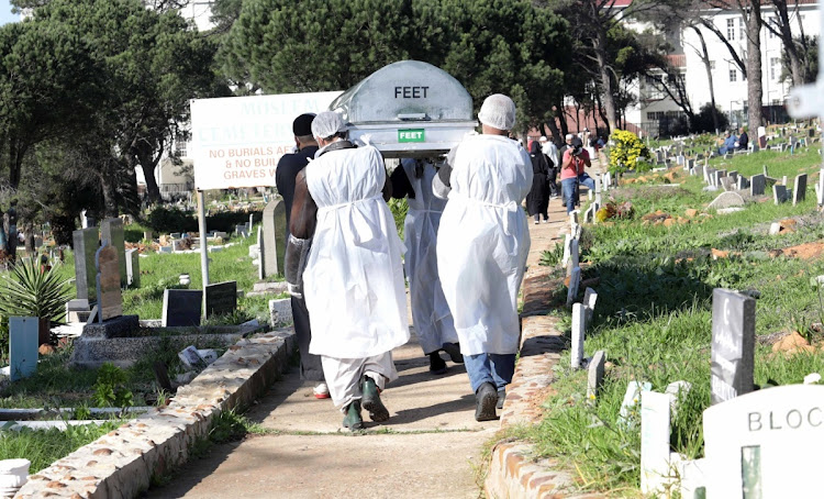 The sons of a Cape Town man who died from Covid-19 carry their father to his grave in Mowbray cemetery, Cape Town.
