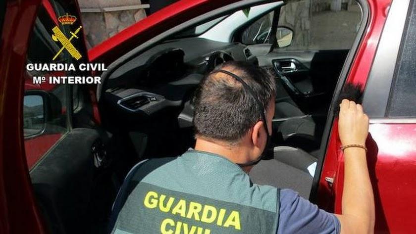 Un agente de la Guardia Civil examina el interior de un vehiculo.