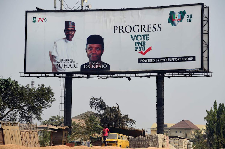 A man walks past a campaign billboard for Nigeria's incumbent president and candidate to his re-election for the ruling All Progressives Congress (APC) President Muhammadu Buhari, and Vice-President Yemi Osinbajo. Picture: AFP/ PIUS UTOMI EKPEI