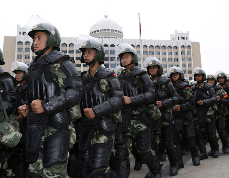 Paramilitary police officers take part in a gathering to mobilise security operations in Xinjiang. Picture: REUTERS