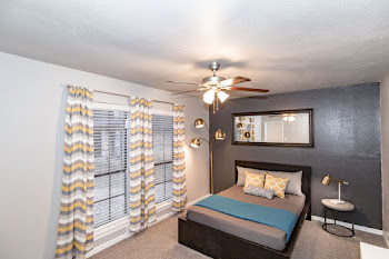 Model bedroom with dark accent wall and ceiling fan