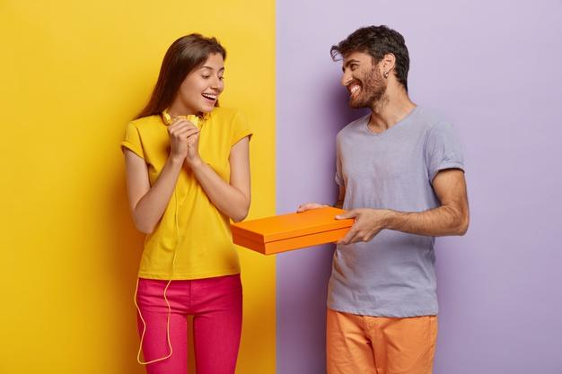 Friendly smiling guy gives cardboard box with surprise to girlfriend, congratulates her with victory. satisfied lady in yellow t shirt and pink trousers happy to get package from close friend Free Photo