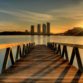 Sunrise over Putrajaya Lake by Nadly Aizat Nudri - Landscapes Waterscapes ( shadow, putrajaya, pier, ray of light, bridge, lakeside, sunrise, still water, golden hour )