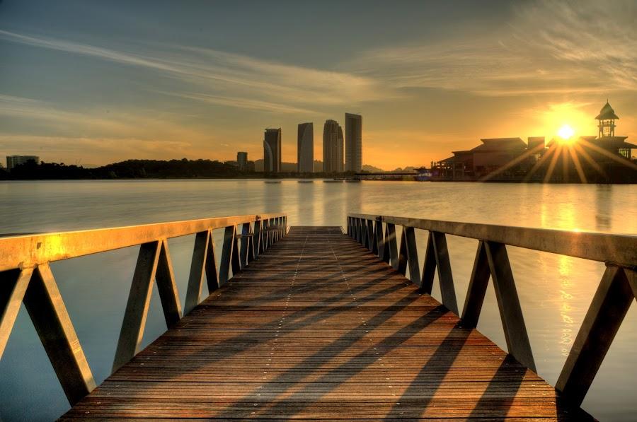 Sunrise over Putrajaya Lake by Nadly Aizat Nudri - Landscapes Waterscapes ( shadow, putrajaya, pier, ray of light, bridge, lakeside, sunrise, still water, golden hour )
