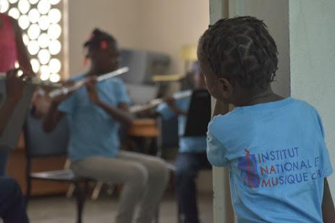 Una niña haitiana mira con curiosidad la clase de flauta