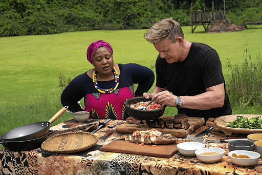 Chef and author Zola Nene observes as British chef Gordon Ramsay tops grilled fish with ushatini, a salsa-like mix of onions and tomatoes.